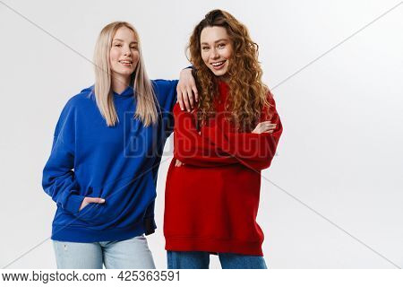 Two smiling young white women friends wearing sweatshirt standing posing isolated over white background