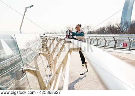 Young healthy sportswoman with prosthetic leg exercising stretching legs outdoors wearing headphone