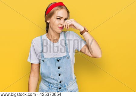 Young caucasian girl wearing casual clothes smelling something stinky and disgusting, intolerable smell, holding breath with fingers on nose. bad smell