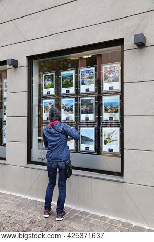 Mandal, Norway - July 17, 2020: Person Analyzes Real Estate Offers Of A Real Estate Agency Window In