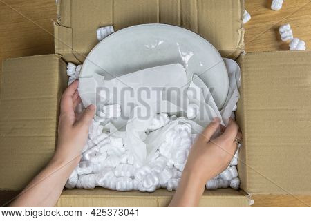 Young Woman Unwrapping Delivery Package,online Shopping Package. Fragile Cardboard Box With Plate At