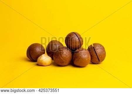 Delicious And High-calorie Macadamia Nut On A Yellow Background.