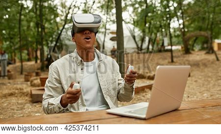 Smiling Young African American Man Wearing Virtual Reality Glasses And Holding Gamepads Near Laptop