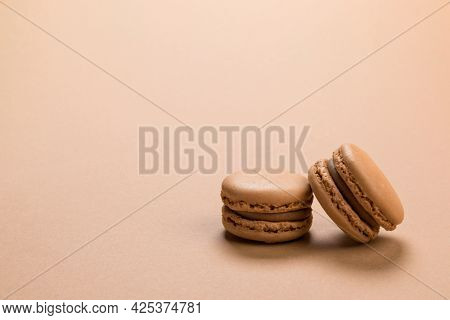 Raspberry flavor French macaron cookies closeup on background of a similar pastel brown colour with copy space