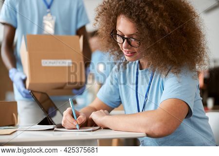 Young Woman Volunteer Making Notes And Guy Carrying Cardboard Box In The Background While Working On