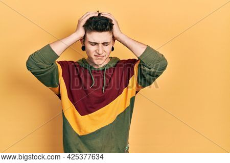 Young caucasian boy with ears dilation wearing casual sweatshirt suffering from headache desperate and stressed because pain and migraine. hands on head.