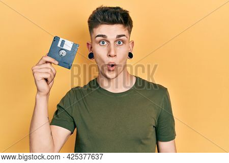 Young caucasian boy with ears dilation holding floppy disk scared and amazed with open mouth for surprise, disbelief face