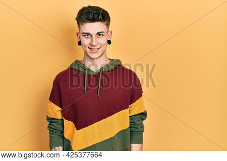 Young caucasian boy with ears dilation wearing casual sweatshirt with a happy and cool smile on face. lucky person.
