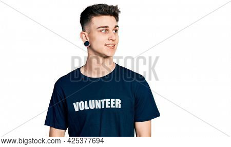 Young caucasian boy with ears dilation wearing volunteer t shirt smiling looking to the side and staring away thinking.