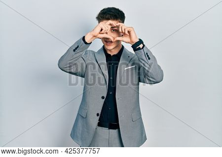 Young caucasian boy with ears dilation wearing business jacket doing heart shape with hand and fingers smiling looking through sign
