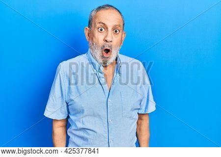 Handsome senior man with beard wearing casual blue shirt scared and amazed with open mouth for surprise, disbelief face