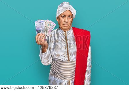 Senior hispanic man wearing sherwani costume holding indian rupee banknotes thinking attitude and sober expression looking self confident