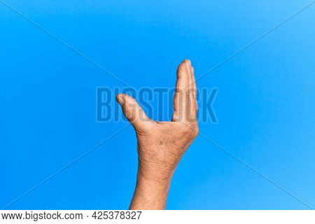 Hand of senior hispanic man over blue isolated background picking and taking invisible thing, holding object with fingers showing space