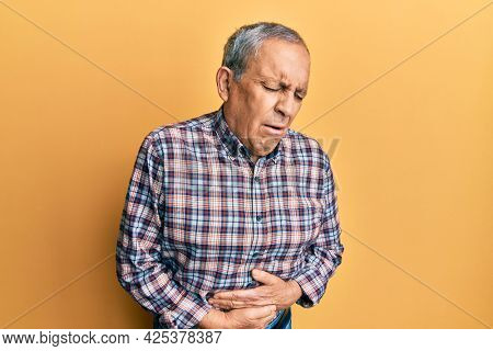 Handsome senior man with grey hair wearing casual shirt with hand on stomach because indigestion, painful illness feeling unwell. ache concept.