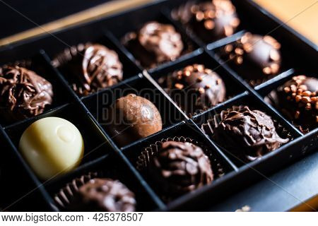Several Variety Of Chocolate Truffles With Chocolaty And Milky Glaze And Golden Sprinkles With Nuts.