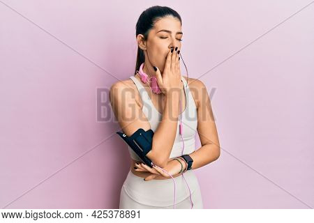 Young hispanic woman wearing gym clothes and using headphones bored yawning tired covering mouth with hand. restless and sleepiness.
