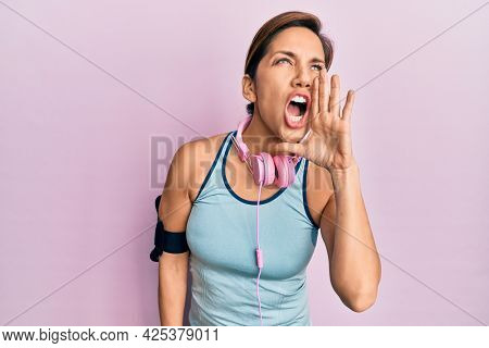 Young latin woman wearing gym clothes and using headphones shouting and screaming loud to side with hand on mouth. communication concept.