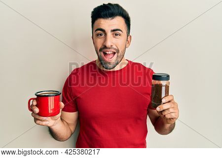 Young hispanic man holding cup of soluble coffee celebrating crazy and amazed for success with open eyes screaming excited.