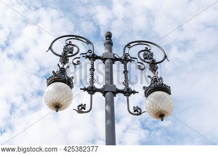 Detail Of Metallic Street Light On The Blue Sky With White Clouds Background. Antique Metallic Stree