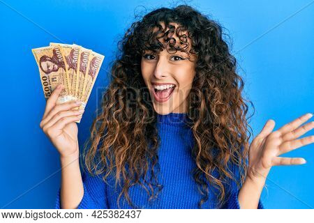 Young hispanic girl holding 5000 hungarian forint banknotes celebrating achievement with happy smile and winner expression with raised hand