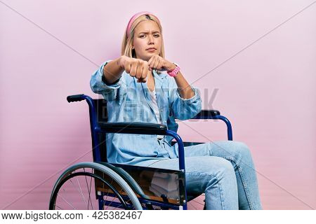 Beautiful blonde woman sitting on wheelchair punching fist to fight, aggressive and angry attack, threat and violence