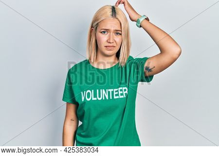 Beautiful blonde woman wearing volunteer t shirt confuse and wondering about question. uncertain with doubt, thinking with hand on head. pensive concept.