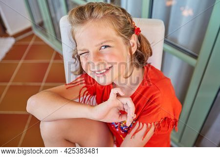 A Beautiful Blonde Girl With A Short Haircut Is Sitting On A Chair, Smiling