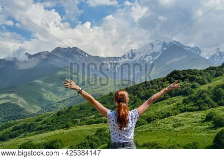 The Girl Looks At The Mountains And Spreads Her Arms To The Sides, There Is Snow On The Tops Of The