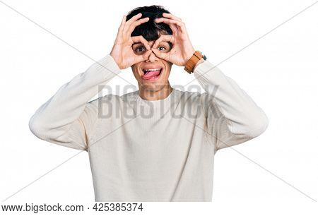 Handsome hipster young man wearing casual winter sweater doing ok gesture like binoculars sticking tongue out, eyes looking through fingers. crazy expression.