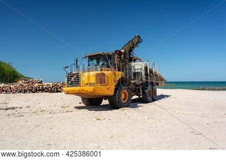 Chalupy, Poland - June 16, 2021: A heavy truck carries a tree on the beach to build breakwaters by the Baltic Sea