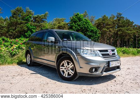 Chalupy, Poland - June 16, 2021: Fiat Freemont SUV parked at forest in Poland. Fiat Freemont is an european version of Dodge Jurney manufactured sience 2011.