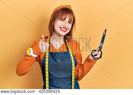 Redhead young woman dressmaker designer wearing atelier apron holding scissors smiling happy and positive, thumb up doing excellent and approval sign