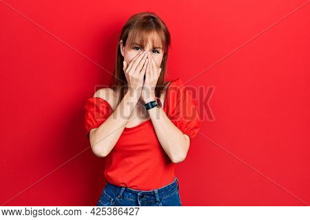 Redhead young woman wearing casual red t shirt laughing and embarrassed giggle covering mouth with hands, gossip and scandal concept