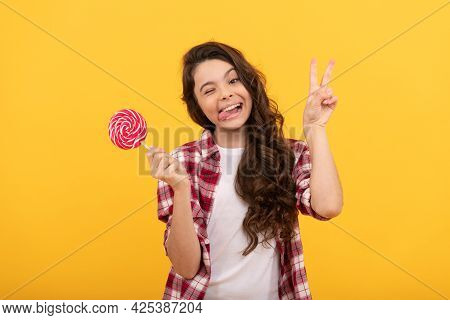 Funny Teen Girl Hold Lollipop Caramel Candy On Yellow Background Show Peace Gesture, Caramel Shop.