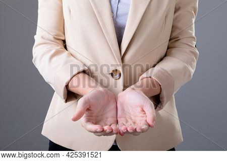 Midsection of caucasian businesswoman showing her hands, isolated on grey background. business technology, communication and growth concept.
