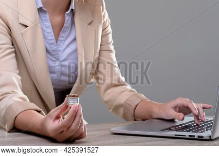 Midsection of caucasian businesswoman holding base of light bulb, isolated on grey background. business, technology, communication and growth concept.