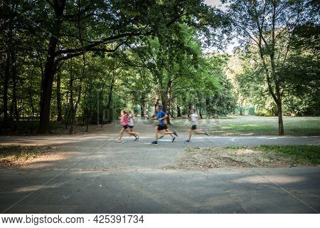 Unrecognizable Joggers Running With A Speed Blur, In Movement, In The Erzsebet Liget Park Of Szeged,