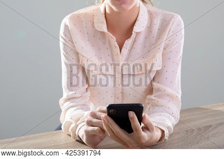 Midsection of caucasian businesswoman using smartphone, isolated on grey background. business, technology, communication and growth concept.