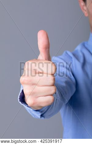Midsection of caucasian businessman with thumb up, isolated on grey background. business technology, communication and growth concept.