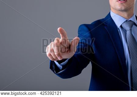 Midsection of caucasian businessman touching virtual interface, isolated on grey background. business technology, communication and growth concept.