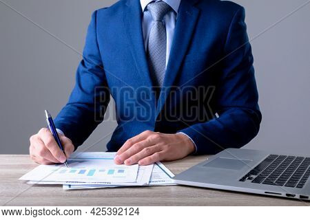 Midsection of caucasian businessman using laptop and taking notes, isolated on grey background. business technology, communication and growth concept.