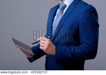 Midsection of caucasian businessman using digital tablet, isolated on grey background. business technology, communication and growth concept.