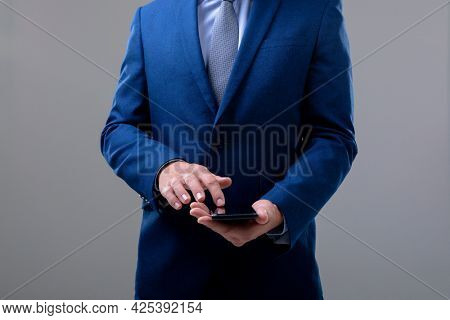 Midsection of caucasian businessman using smartphone, isolated on grey background. business technology, communication and growth concept.