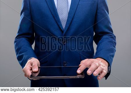 Midsection of caucasian businessman using tablet, isolated on grey background. business technology, communication and growth concept.