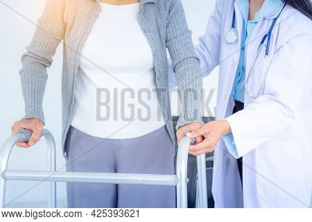 Close Up Of Female Doctor Wearing Medical Mask Supporting Senior Woman By Using Walker. Elderly Pati