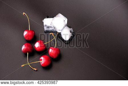 A Pile Of Ripe Cherries And Cubes Of Melted Ice On A Black Background.