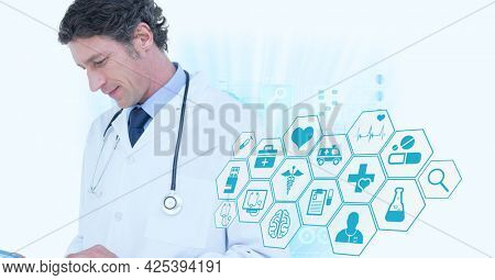 Male senior doctor using digital tablet against multiple medical icons on white background. medical research and science technology concept