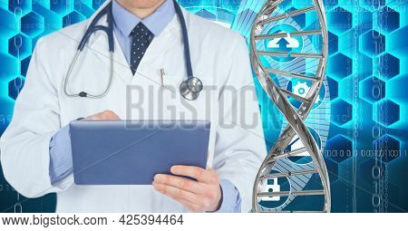Mid section of male doctor using digital tablet against dna structure and medical data processing. medical research and science technology concept