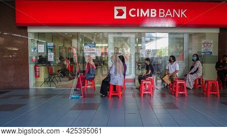 Labuan Ft,malaysia-may 17,2021:people Waiting In A Queue Outside Malaysia Commercial Bank With Socia