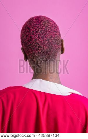 Portrait Of A Black Short Haired Woman Back In Front Of A Pink Background